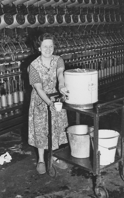 Women serving tea in front of a winding machine image