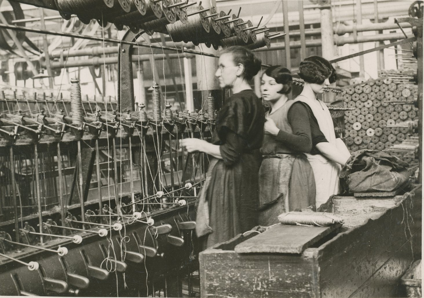 Winding machine with two young, and one old, female attendants image
