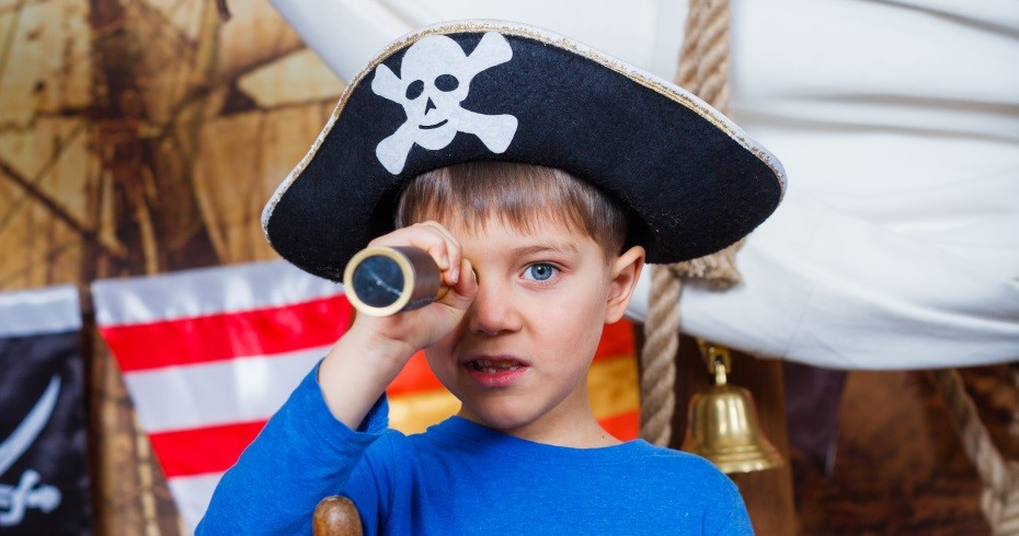 wee boy dressed up in a pirate tricorn, holding a telescope