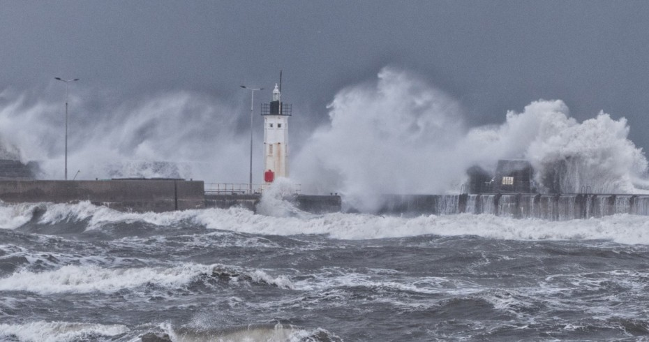 photograph of pier with dramatic waves crashing over it