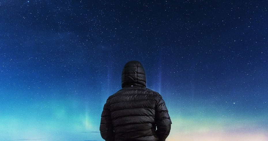 man with back to camera looking up at starlit night sky