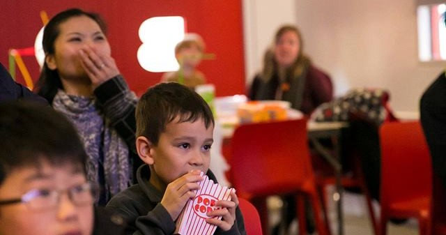 image of children and parents eating popcorn in the red box at verdant works