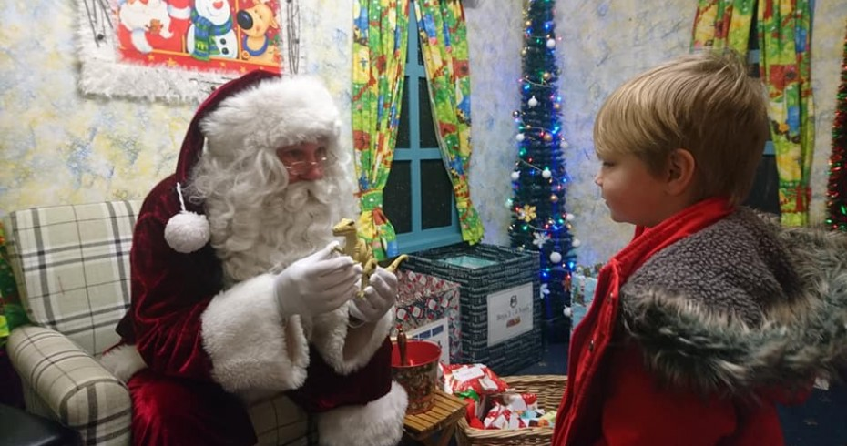santa in a grotto speaking to a little boy