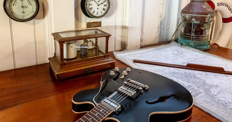 image of guitar with kit from discovery in background