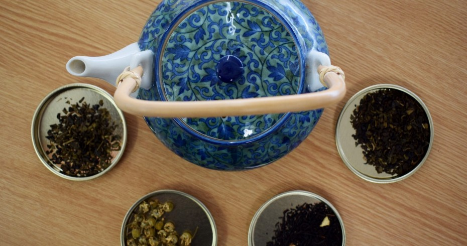 image of tea pot surrounded by containers of various teas