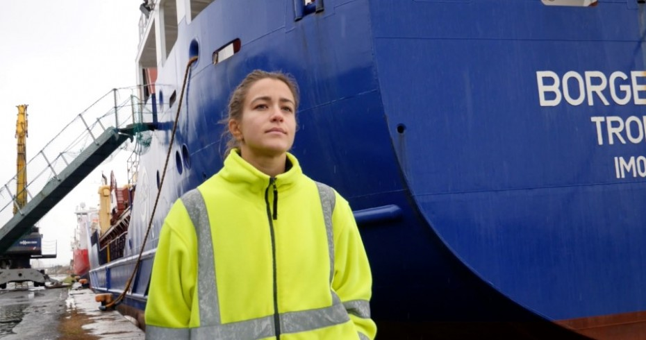 image of woman in safety jacket standing next to huge blue boat