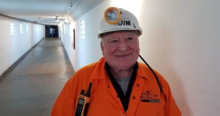 jim lennie tour guide in orange boiler suit wearing pit helmet