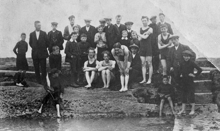 black and white photo of group of men and boys at tidal pool