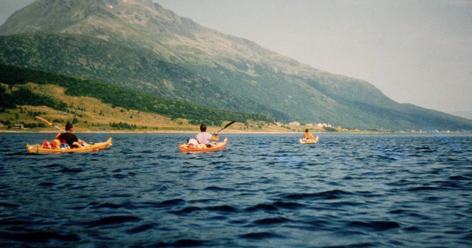 image of three kayaks on blue water with hill in background