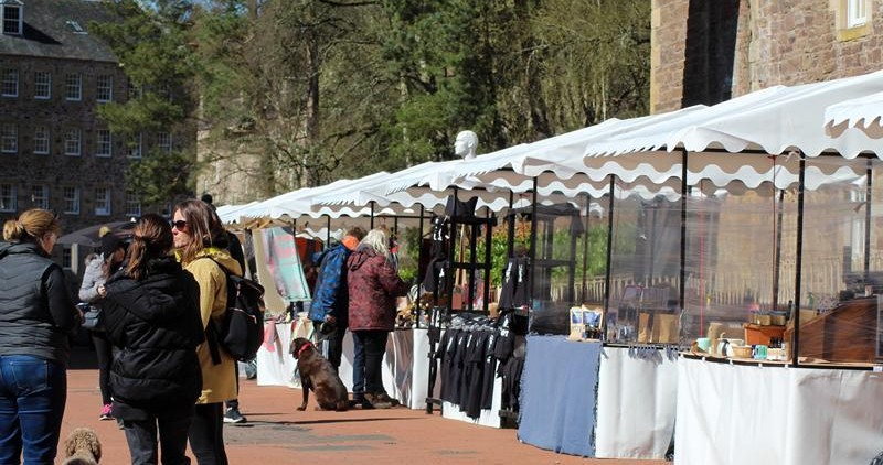 people visiting stalls at outdoor market at new lanark