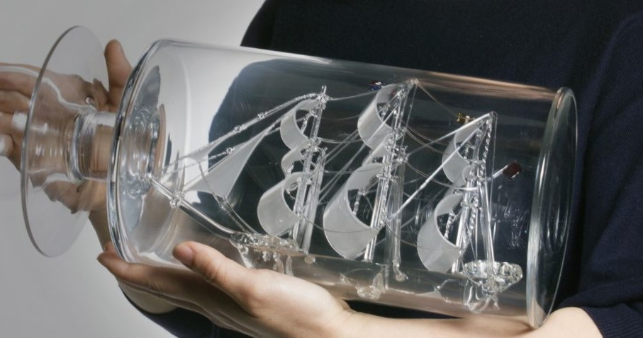 glass ship in bottle being held by human hands
