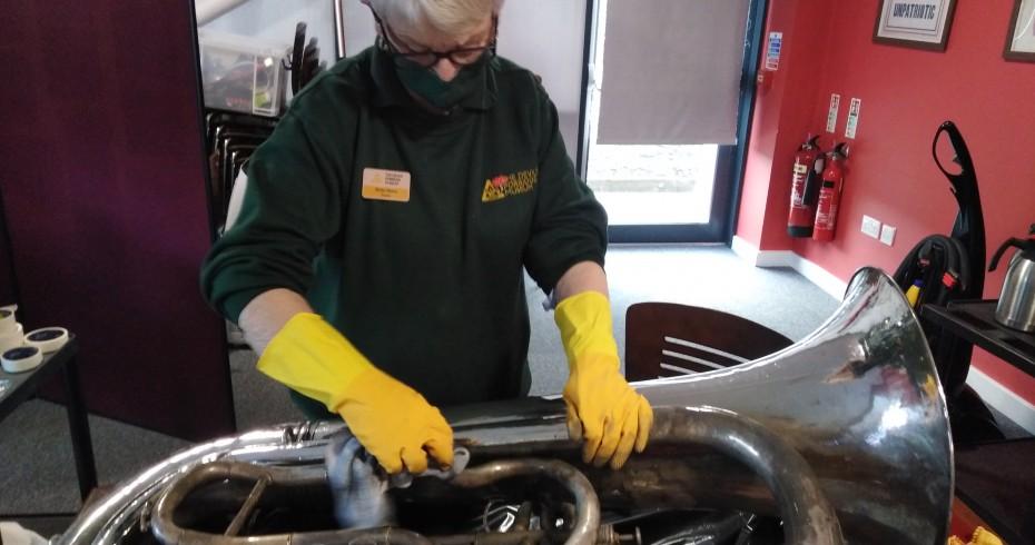 museum workforce cleaning tuba at devil's porridge museum 930