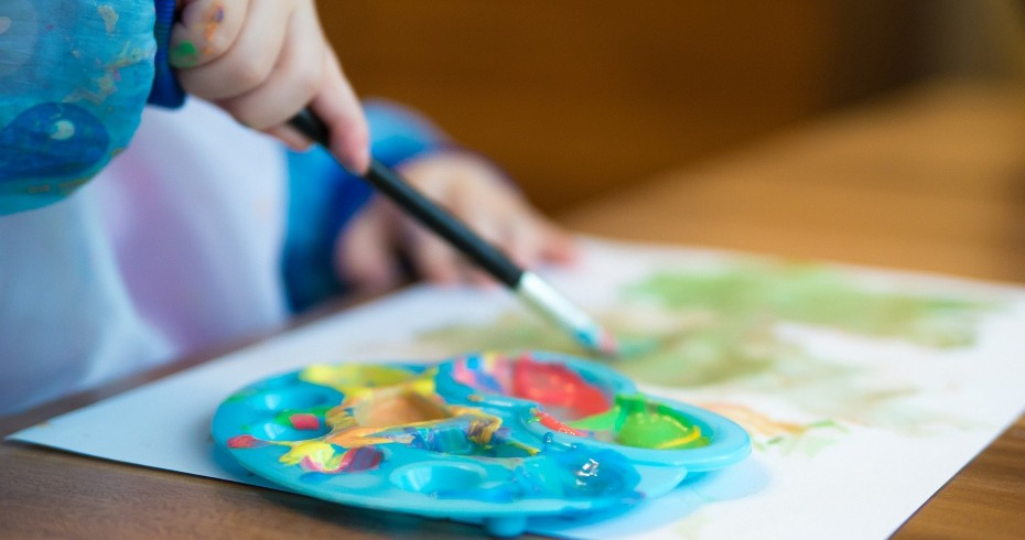 arts and crafts childs hand holding paint brush with paint palette